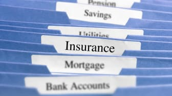 File folders with different financial products written on them, including insurance