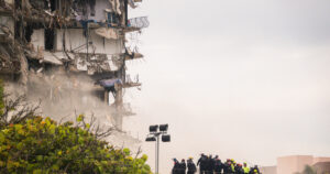 South Florida Urban Search and Rescue personnel work atop rubble at the partially collapsed 12-story Champlain Towers South condo building in Surfside, Florida, on June 25. Insurers were already skittish after losses from repeated hurricanes, and the recent condo collapse brought new insecurity: How long will Florida's coast be insurable? (Angel Valentin / The New York Times)